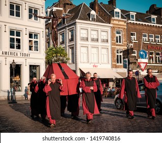Maastricht, Netherlands - June 9, 2019: Religious procession with a congregation carrying a statue of Jesus Christ through the street of Maastricht.