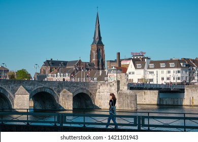 Maastricht, Netherlands - June 9, 2019: View of Maastricht. Woman walks by a bridge over the Maas (Meuse) River and near a church