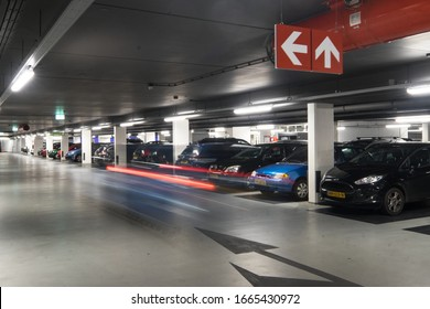 MAASTRICHT, NETHERLANDS MARCH 02 2020: Underground parking garage with parked cars and stripes of light from a car passing by