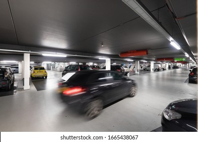 MAASTRICHT, NETHERLANDS MARCH 02 2020: Underground parking garage with parked cars and a car passing by (motion blur)