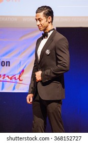 MAASTRICHT, THE NETHERLANDS - OCTOBER 25, 2015: Male fitness model Ali Dalili from Iran dressed in suit shows his best on stage at the World Grandprix Bodybuilding and Fitness of the WBBF-WFF