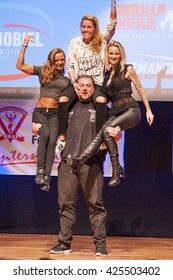 MAASTRICHT, THE NETHERLANDS - OCTOBER 25, 2015: Belgium strongman Jimmy Laureys lifts girls on stage at the World Grandprix Bodybuilding and Fitness of the WBBF-WFF