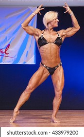 MAASTRICHT, THE NETHERLANDS - OCTOBER 25, 2015: Female fitness model Gerbel Mikk flexes her muscles and shows her physique in a front double biceps pose on stage at the World Grandprix Bodybuilding