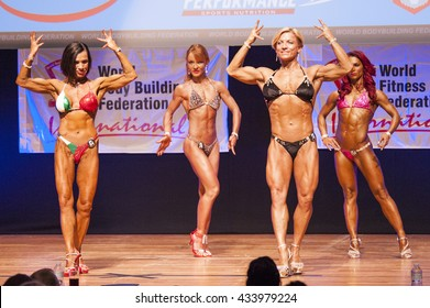 MAASTRICHT, THE NETHERLANDS - OCTOBER 25, 2015: Female bodybuilders Gerbel Mikk and Sonja den Breems-Tanamal flex their muscles and show their best physique in a front double biceps pose on stage