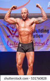 MAASTRICHT, THE NETHERLANDS - OCTOBER 25, 2015: Male bodybuilder Erik Stobbe shows his best front double biceps pose at the World Grandprix Bodybuilding and Fitness of the WBBF-WFF