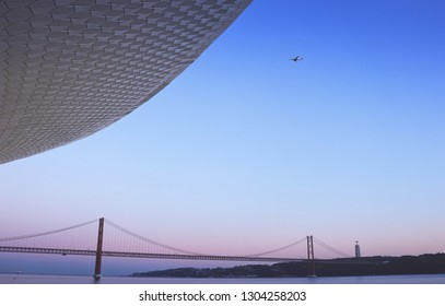 The MAAT - Museum of Art, Architecture and Technology with a Airplaine arriving to lisbon with the 25 of april bridge in background at the sunset. Lisbon Portugal