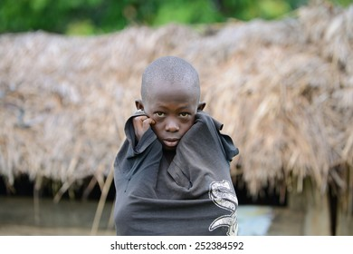 Mabamba Swamp, Wakiso District/Uganda  May 23 2014: Waiting for his father to return with food for the family, a young boy stands in the rain in a small fishing village in Uganda.