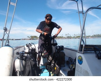 MABUL, SABAH 2 JULY 2014 : Dive instructor preparing diving equipment on a speed boat. Mabul is one of the best diving spot in the world.