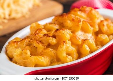Mac and Cheese, American pasta in red casserole, closeup.