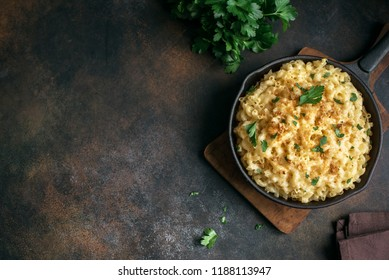 Mac and cheese, american style macaroni pasta with cheesy sauce and crunchy breadcrumbs topping on dark rustic table, copy space top view