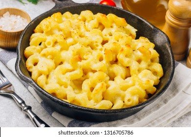 Mac and cheese, american style macaroni baked pasta with cheesy sauce in pan, light background, Selective focus