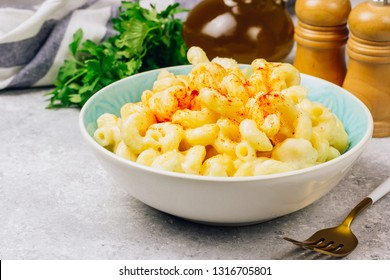 Mac and cheese, american style macaroni pasta with cheesy sauce in blue bowl, light background, Selective focus
