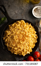Mac and cheese in a cast iron pan baked with breadcrumbs overhead shot, rustic style