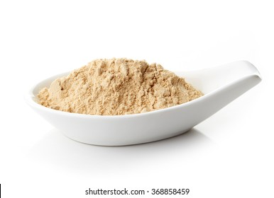 Maca powder in white porcelain spoon on white background