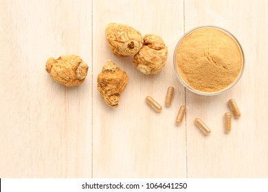 Maca root and maca powder and capsules, on white wooden background. (Taken from above)