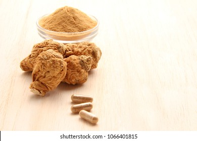 maca root and maca powder and capsules on white wood background