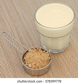 Maca root powder and drink in a glass over bamboo. Health and body building food.