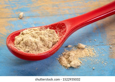maca root powder on on a red stoneware teaspoon against grunge wood, healthy superfood concept