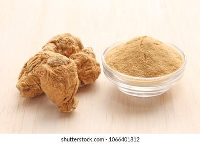 maca root and maca powder on white wood background