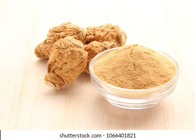 maca root and maca powder on white wood background