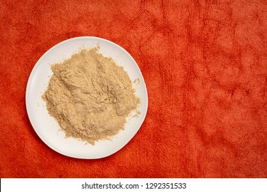 maca root powder on white ceramic plate against red textured paper with a copy space