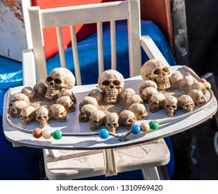 Macabre display of gothic skulls consisting of ten heads in a circle sitting on a white wooden child's high chair tray. The decorative red, yellow, green and blue beads are a weird juxtaposition.
