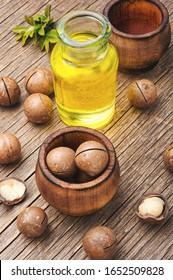 Macadamia-Nussöl und Macadamia-Nuss auf Holzhintergrund.Glasflaschen mit Macadamia-Öl
