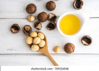 The Macadamia Nut Oil and peeled macadamia nut   on white table ,use for Healthy Skin and Hair and Natural Healing Oil Treatment , overhead and top view