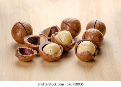 Macadamia nut with shell on wooden background