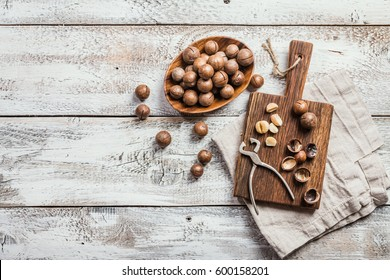 Macadamia nuts on cutting board over white wooden table, top view