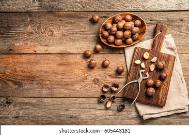 Macadamia nuts on cutting board over wooden table, top view