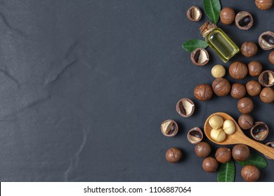 Macadamia nuts on wood spoon with macadamia nut oil on black stone background. superfood and healthy food concept, top view and copy space