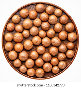 macadamia nuts in shells on on a round wooden tray isolated on white