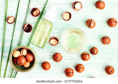 Macadamia nuts with vegan pure oil in bottle for cosmetic use in natural beauty treatment, view from above light blue wooden table.