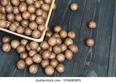 macadamia nuts in a wooden bowl close up on a dark background