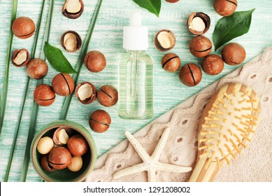 Macadamia oil in bottle top view on blue wooden table with nuts for holistic hair care, beauty serum, brush & towel