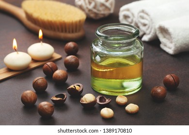 macadamia oil in a glass bottle, macadamia nuts, objects for spa on a brown background