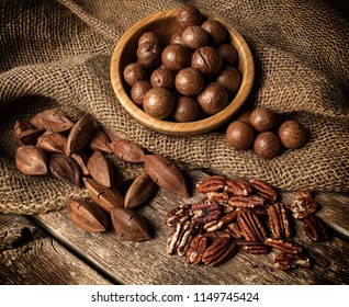 Macadamia, Pecan and Pili nuts on wooden table.