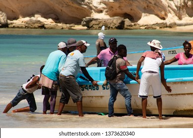 Macao Beach, Bavaro, Dominican Republic, 10 april, 2019 / Group of fishermen pushing a wooden fishing boat on the shore after the fishing tour.