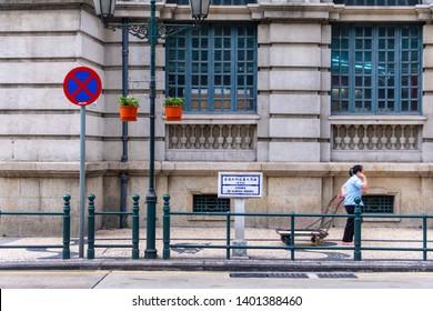 """Macao, China - APR 2019: The road sign of the avenue """"Avenida de Almeida Ribeiro"""" (in English means """"Almeida Ribeiro Avenue""""), and background is Macau Post building"""