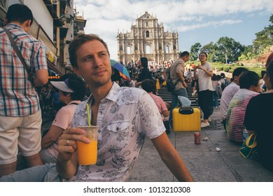 Macao, China. August 30, 2017. Young man sitting by the Ruins St.Paul church eating Pastel De Nata and drinking papaya juice.