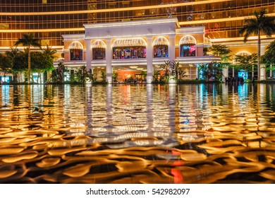 Macao, China - January 24, 2016: Macau Wynn Palace entrance group night view displays water reflections of architectural illumination on the surface of the Performance Lake