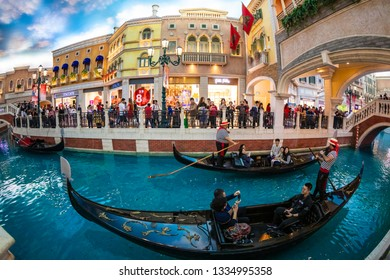 """Macao China-Feb 3, 2019: The Grand Canal Shopping Center in Venetian, the world's largest casino, is crowned with artificial """"blue sky and white clouds"""" and tourists ride on the Venetian boat Gondola."""