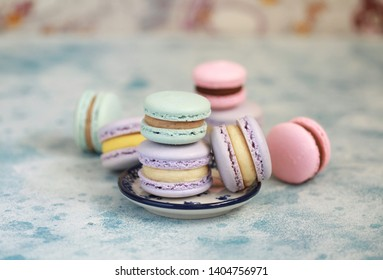Macaron or macaroon on blue background, colorful almond cookies with different filling. Selective focus