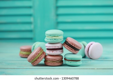 Macaron or macaroon on turquoise background, colorful almond cookies with different filling. Selective focus