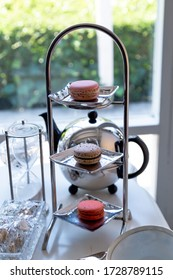 Macaron on a shelf for sweets and teapots made of stainless steel in an antique shape Put on the white table The background is a clear window that can be seen outside.