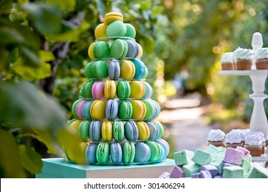 Macaron tower or pyramid and cupcakes on sweet dessert table