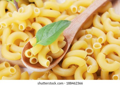 macaroni and basil in wooden spoon