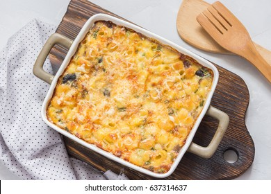 Macaroni and cheese in a backing dish on wooden board. Top view.