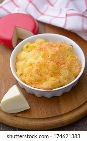 Macaroni and cheese in a baking dish on a cutting board